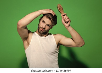 Macho with bearded face and haircut in white singlet. Man brush hair with hairbrush on green background. Haircare, hairstyle concept. Fashion, underwear, style. Beauty, grooming, hygiene.