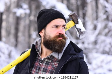 Macho in black hat with yellow ax. Guy with thoughtful face with forest covered by snow on background. Masculinity and strength concept. Hipster woodsman concept. Man with beard and mustache holds axe