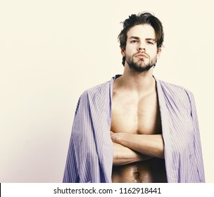 Macho in blue bathrobe with crossed arms. Morning concept. Man with beard in blue dressing gown on white background, copy space. Muscular guy with sexy muscular chest in home or bath clothes.