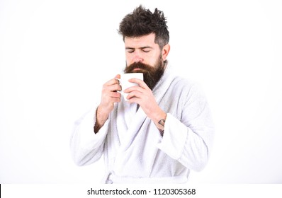 Macho drowsy, sleepy face drinks coffee in morning enjoying aroma. Man with beard and disheveled hair stands in bathrobe, holds mug with tea or coffee, white background. Morning rituals concept.