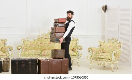 Macho elegant on strict face carries pile of vintage suitcases. Butler and service concept. Man with beard and mustache wearing classic suit delivers luggage, luxury white interior background.