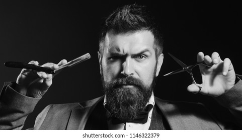 Macho in formal suit cuts and shaves beard and moustache. Man with beard holds shaving razor and scissors. Businessman with strict face on dark blue background. Business and barbershop service concept