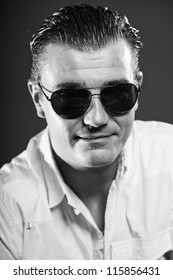 Macho handsome man with short brown hair wearing white shirt and sunglasses. Mafia type. Good looking. Fashion studio portrait. Isolated on grey background. Glamour black and white portrait.