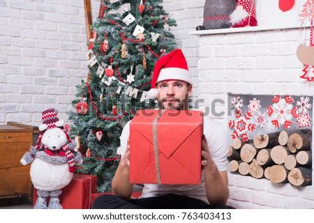 74a57c3e15725 Macho hold present box with toy bear at xmas tree. Man in santa hat sit