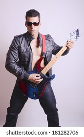 Macho man with electric guitar isolated in studio shot image