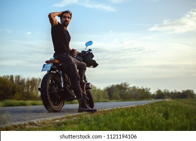 Macho man sitting on his bike in the middle of the road and holding his hair