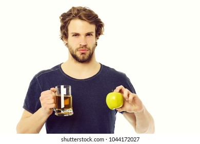Macho man with strong face holding glass of beer and green apple, isolated on white background. Concept of healthy choice
