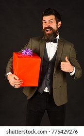 Macho in retro suit presents wrapped gift. Birthday present concept. Man with beard holds present. Businessman with cheerful face and red gift box shows thumbs up on brown background.