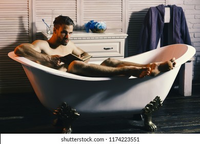 Macho sitting naked in bathtub and reading book. Guy in bathroom with toiletries and chair on background. Sex and relaxation concept. Man with beard and suspicious face.