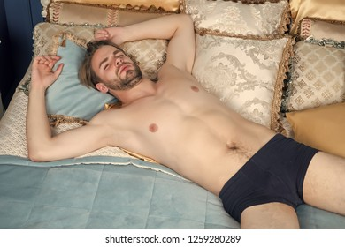 Macho sleep in blue bed. Man with sexy body in briefs in bedroom. Fashion, male underwear. Dream, slumber concept.