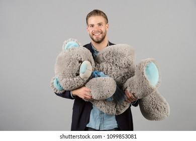 Macho smile with grey teddy bear. Happy man big animal toy. Man smile with big animal toy. Gift and present concept. Fashion and style. Birthday or anniversary and holiday celebration.