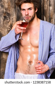 Macho tousled hair degustate luxury wine. Drink wine and relax. Guy attractive relaxing with alcohol drink. Man sexy chest wet skin after bath hold wineglass. Bachelor enjoy wine after bath.