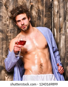 Macho tousled hair degustate luxury wine. Drink wine and relax. Guy attractive relaxing with alcohol drink. Bachelor enjoy wine after bath. Man sexy chest wet skin after bath hold wineglass.