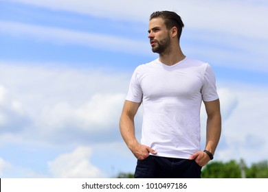 Macho wearing pants and white tshirt. Male body with sexy torso. Man with unshaved and thoughtful face on clear sky background. Health and sexuality concept. Man with wrist tracker looking away.