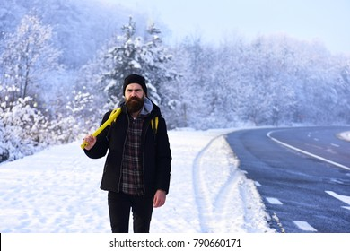 Macho in winter clothes with backpack and yellow ax. Man with beard and mustache holds axe. Guy with strict face with snow and road on background. Wanderlust and working tools concept.