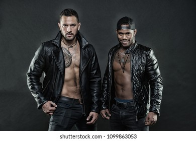 Machos with muscular torsos look attractive in leather jackets, dark background. Men on confident faces with bristle. Masculinity and brutality concept. Men with sexy muscular torsos look brutally.
