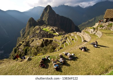 MACHU PICCHU, CUSCO, PERU - AUGUST 2: Group of tourists resting after a mountain hike to pre-Columbian 15th-century Inca site of Machu Picchu on August 2, 2011 in Cusco region, Peru.