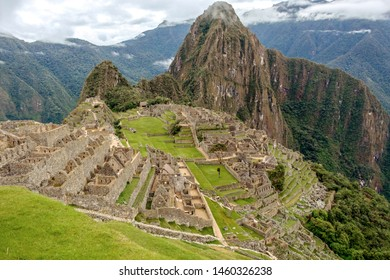 Machu Picchu Incan citadel, abandoned ruins of buildings, walls, plazas, terraces, and ramps reclaim the steep mountainous terrain of the Andes Mountains in Peru, above Urubamba River Sacred valley