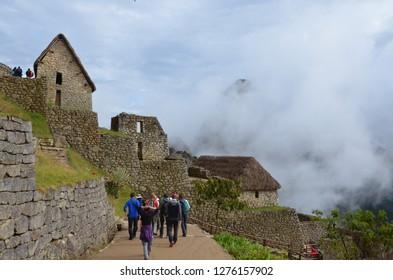 MACHU PICCHU / PERU, August 16, 2018: Tourists walk amid the ruins of Machu Picchu.