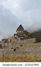 MACHU PICCHU / PERU, August 16, 2018: Tourists explore near the guardhouse in Machu Picchu