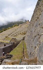 MACHU PICCHU / PERU, August 16, 2018: Tourists walk past a canal in ruins of Machu Picchu.