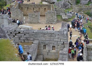 MACHU PICCHU / PERU, August 16, 2018: Tourists explore amid the ruins of Machu Picchu.