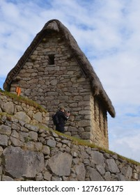 MACHU PICCHU / PERU, August 16, 2018: A tourist takes a photography from behind guardhouse in Machu Picchu ruins
