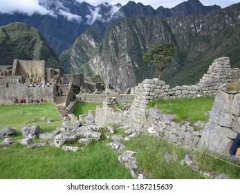 Machu Picchu, Peru - June 10, 2017: Crumbling stone block walls watched over by the mountains at Machu Picchu.
