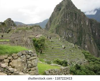 Machu Picchu, Peru - June 10, 2017: The  majestic mountain stands guard over the terraces and ruins of Machu Picchu.