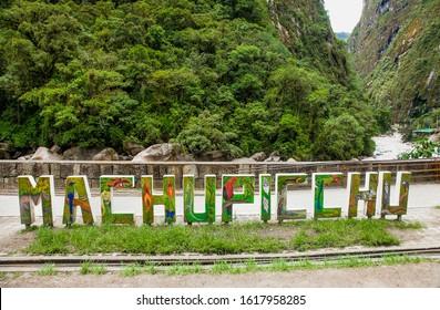 Machu Picchu Pueblo, Peru - Jan 8, 2019: Sign of Town Name at the Roadside of Machupicchu Pueblo or Aguas Calientes with Urubamba river in back,  Peru,