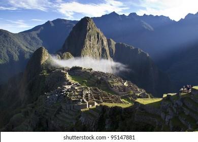 Machu Picchu at sunrise with clouds