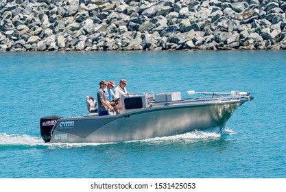 Mackay, Queensland, Australia - October 2019: Three men in a small speed boat on their way out to the ocean for a day of fishing