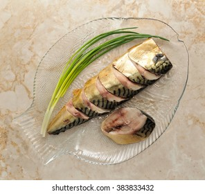 Mackerel on a plate in the form of fish. Smoked mackerel cut into pieces on a platter with green onions. The view from the top.
