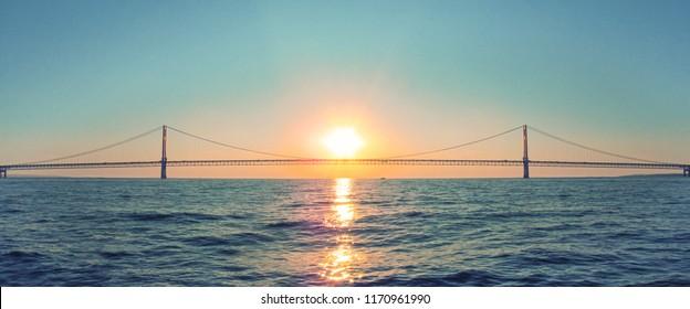 Mackinac Bridge in Michigan at sunset. Horizontal panoramic view of a long steel suspension bridge located in the Great lakes region of North America.