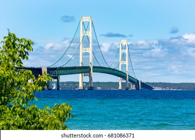 The Mackinac Bridge on a summer day. A suspension bridge spanning the Straits of Mackinac to connect the Upper and Lower Peninsulas of Michigan. Puffy clouds in a blue sky