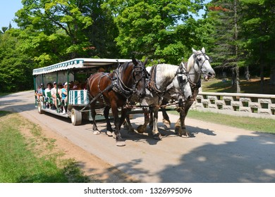 Mackinac Island, Michigan, USA, August 16, 2018: View of the city street at three horse cart service transporting people.