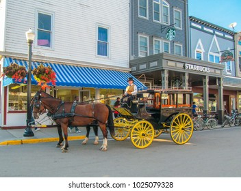 MACKINAC ISLAND, MICHIGAN, USA - September 23,  2017. Horse-drawn carriage. Retro horse Cart with Coachman on the street with old houses in the city center.
