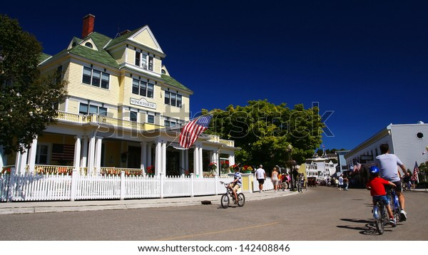 MACKINAC, USA-AUG 14: Unidentified people ride bicycles to see village of Mackinac Island on August 14, 2007 in Michigan, USA. Here located in Lake Huron is an island covering 3.8 square miles' area.