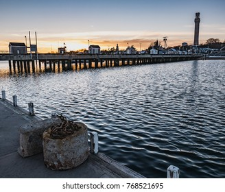 MacMillan Pier and the Pilgrim Monument are set against sunset skies in this Provincetown winter scene.
