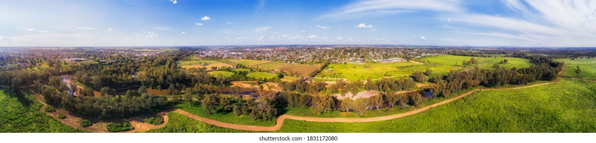Macquarie river flowing around Dubbo city in Great Western Plains of NSW, Australia - wide aerial panorama.