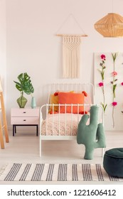 Macrame on the wall of cozy girl's bedroom with flower board and single metal bed with pillows, real photo with copy space