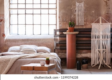 Macrame in a wabi sabi bedroom interior with a bed, table and stand with a plant. Real photo
