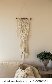 Macrame wall art hanging in the beige interior in beige interior hanging over sofa with green plant in iron vase  placed at he side table