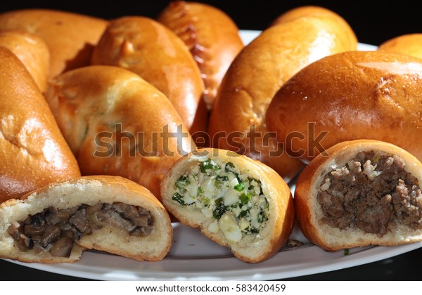 Macro appetizing baked pies with a stuffing on a dark background studio