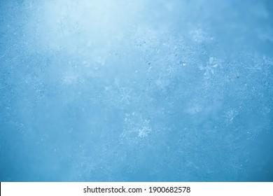 Macro background of fresh snowflake texture on a blur.