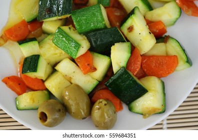 Macro background with healthy steamed mediterranean vegetables and olives. Zucchini, carrot, olives and onion