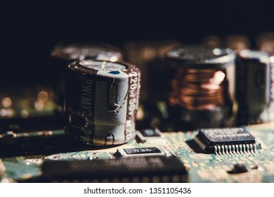 Macro of Big capacitor and inductor installed on a green circuit board. Capacitor store charges and release energy when needed