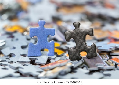 Macro of black and blue puzzle pieces on a pile of jigsaw pieces. Shallow depth of field