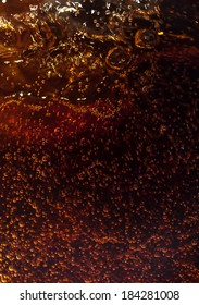 Macro black bubbles on the glass wall of cola