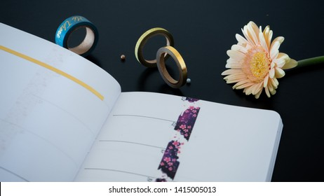 Macro of - Bullet journal - Planer - arranged on black desktop with a flower and decorative tape with perls